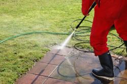 Handyman using a pressure washer on patio tiles